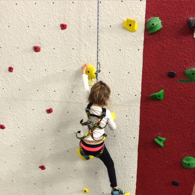 Organic Runner Girl feeling proud on the climibing wall.